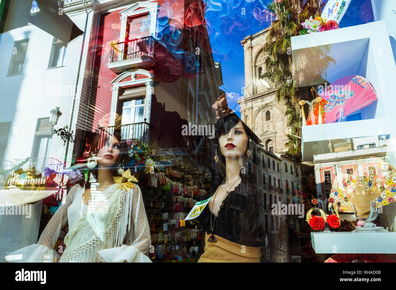 Granada, Andalusia, Spain : Window display with female mannequins in Rocio Flamenco fashion and reflections of the cathedral and Granada historic cent - Stock Image