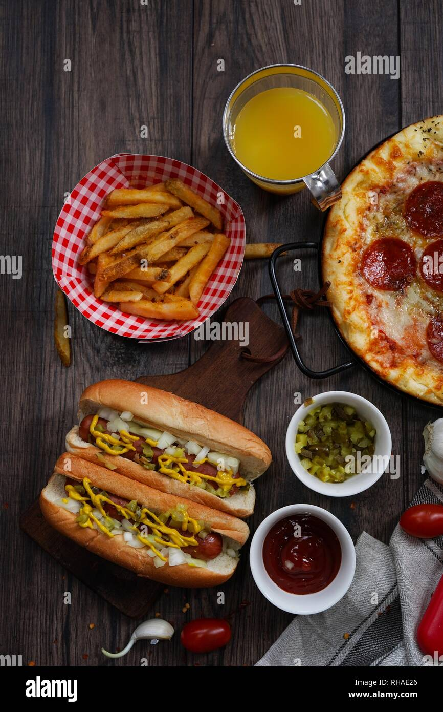 Party game day food Homemade Pizza hot dogs fries juice and dips - Super bowl food concept overhead view Stock Photo
