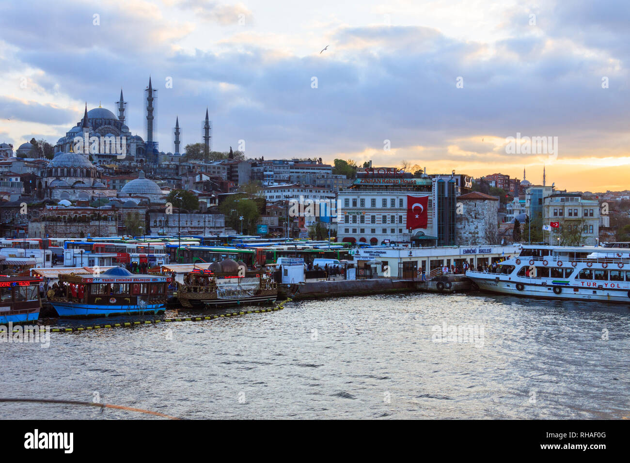 Istanbul, Turkey : Cityscape at sunset with the Suleymaniye mosque and the floating fish restaurants on the Golden Horn. - Stock Image