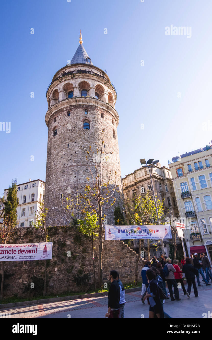 Istanbul, Turkey : People walk past the Genoese built Galata Tower (1348) in the historic Galata (Karaköy) quarter within the Beyoğlu (Pera) district. - Stock Image