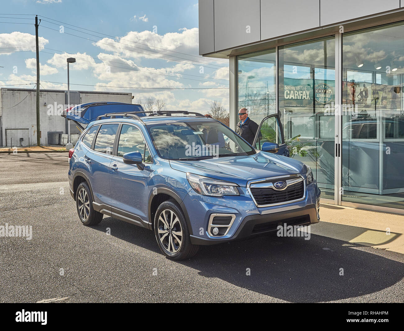 new blue 2019 subaru forester suv at the dealership with a salesman and customer in montgomery alabama usa