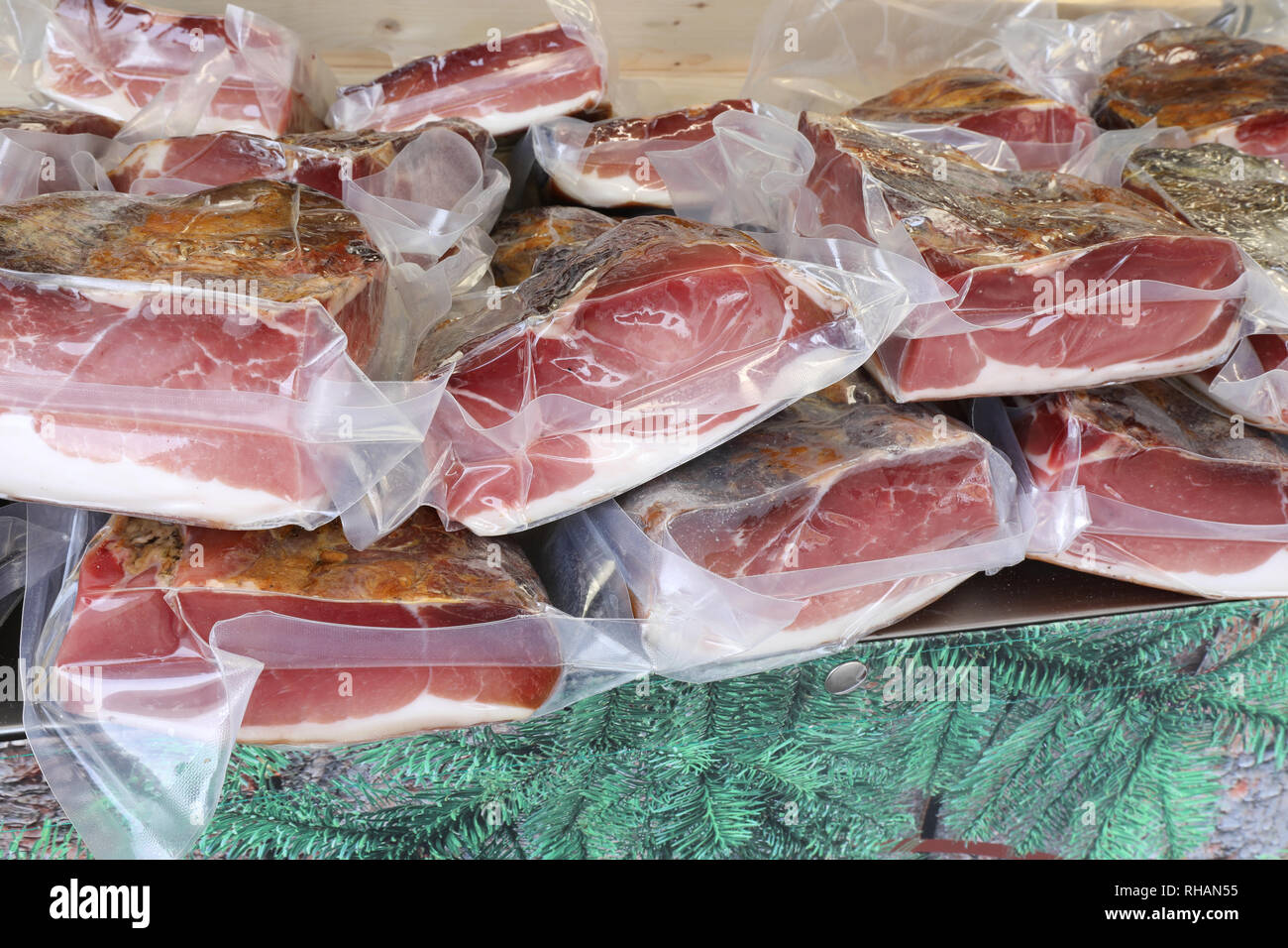 smoked sausages under vacuum for retail sale in the local market - Stock Image