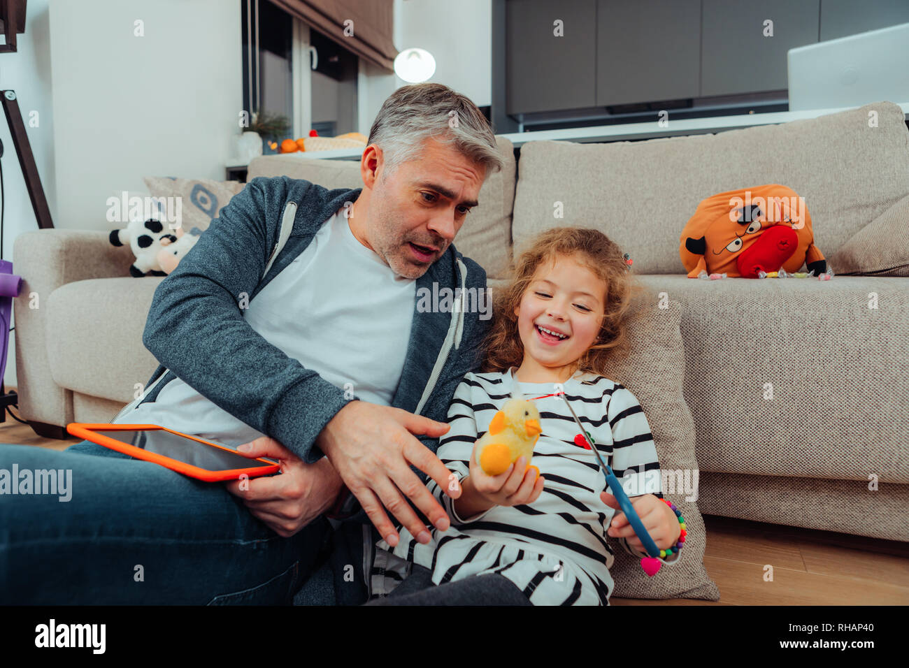 Handsome grey-haired tall father with a red watch on his hand looking shocked Stock Photo