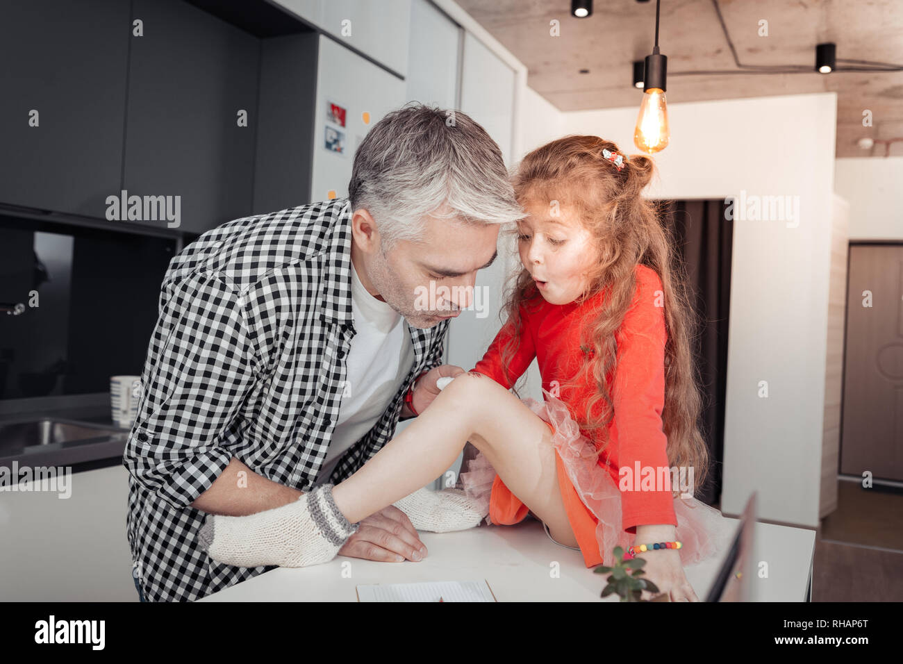 Pretty small long-haired girl and her father looking concentrated - Stock Image