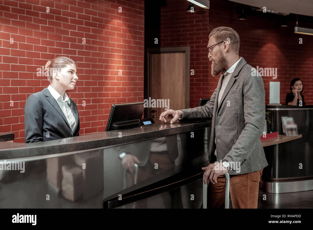 Pleased young manager talking to her visitor - Stock Image