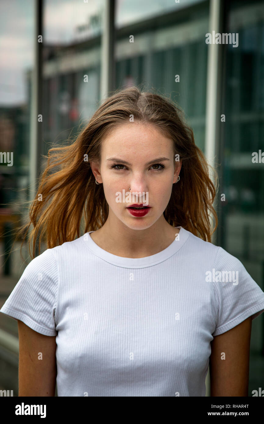 Young pretty woman wearing red lipstick and a white t-shirt posing in urban setting. Looking at camera. Medium shot. Stock Photo