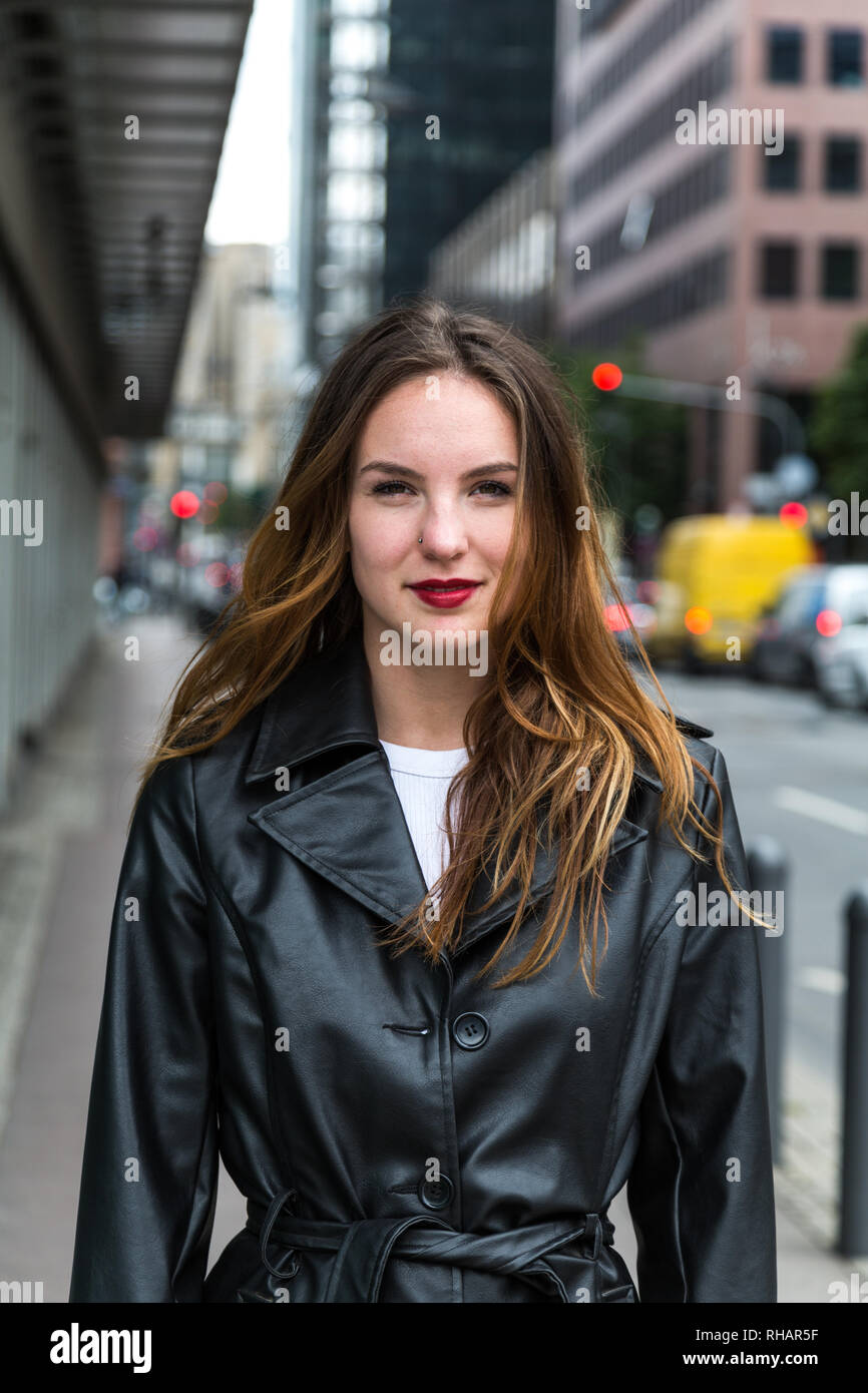 Attractive young woman wearing a black trench coat looking at the camera. Waist up. - Stock Image