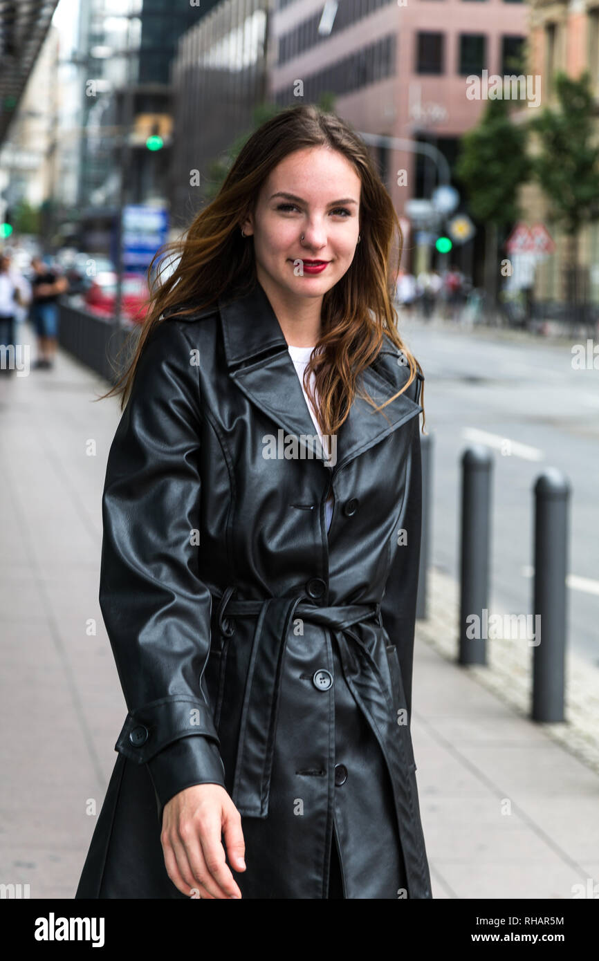 Attractive young woman wearing a black trench coat posing on a city street. Three quarter length. - Stock Image