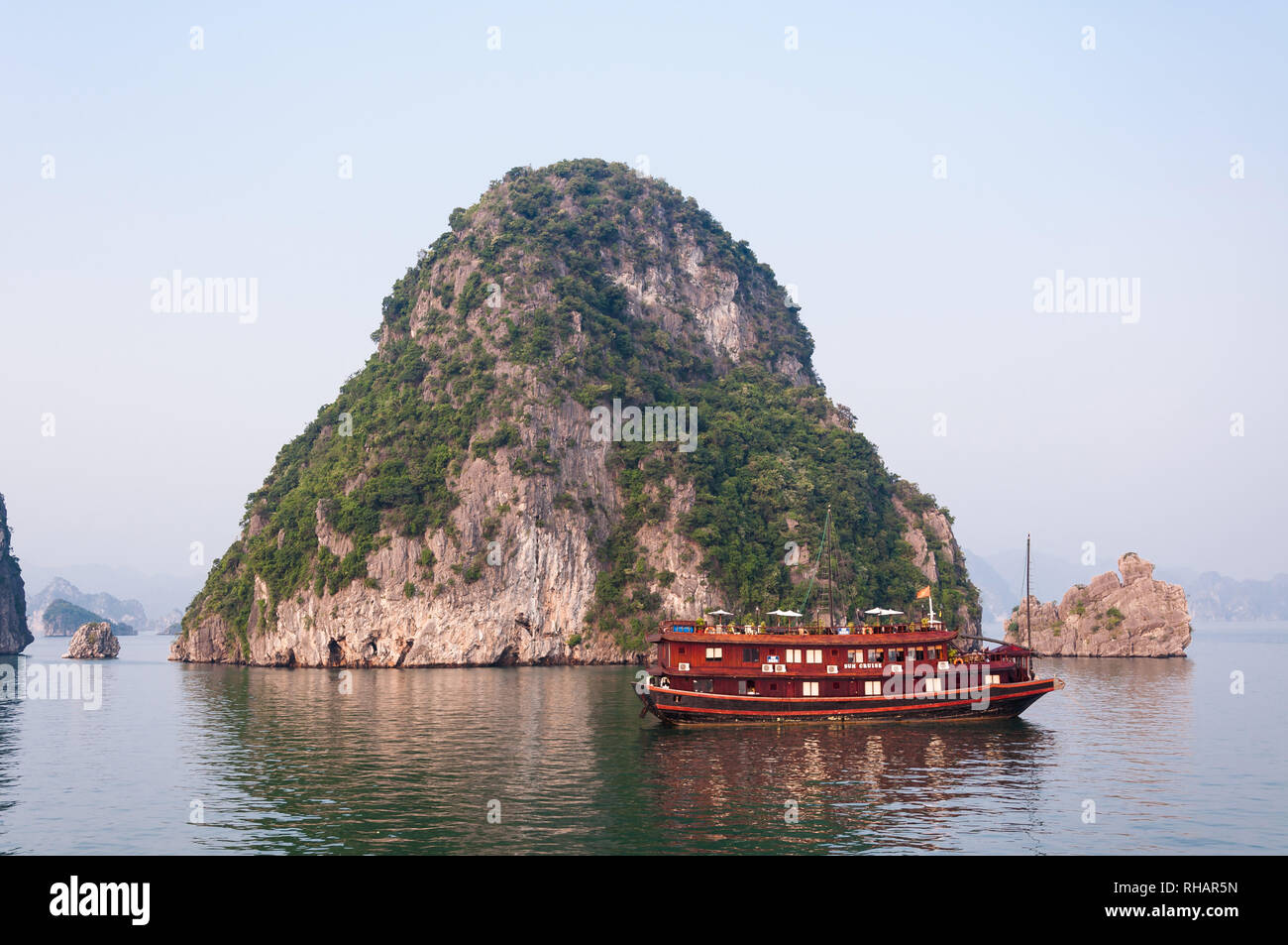 A wooden tourist junk boat anchored by a limestone karst island in early morning light, Halong Bay, Vietnam - Stock Image