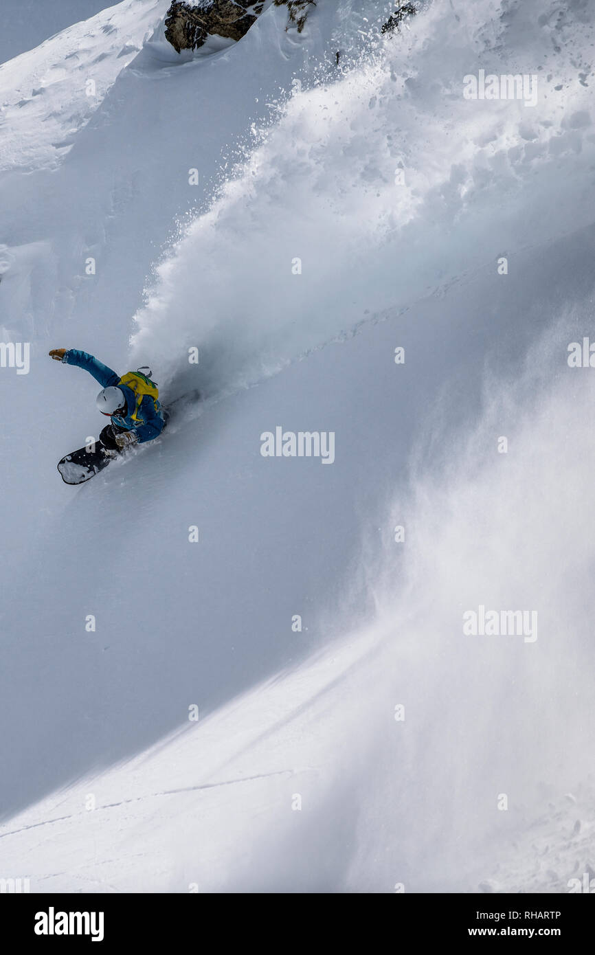 A male snowboarder slashes a turn sending snow spraying behind him off-piste in the French ski resort of Courchevel. - Stock Image