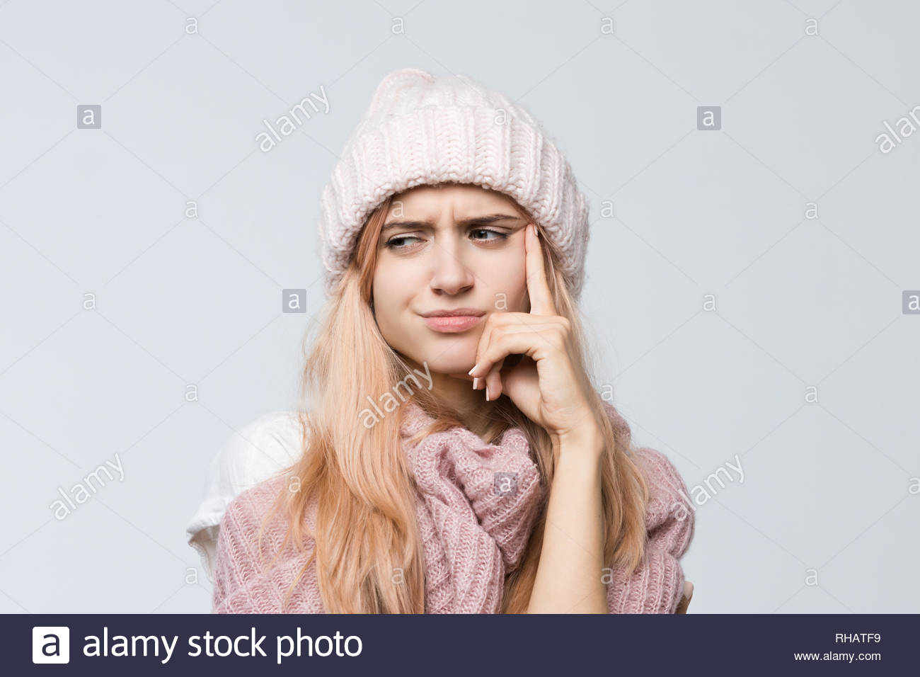 Indoor portrait of cute girl in a pink sweater and white hat frowning face, presses hand to cheek, looks aside with pensive expression/ doubts. - Stock Image