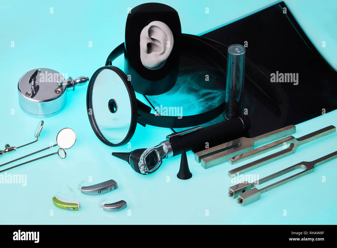 Modern hearing aids on ENT tools background, soft focus - Stock Image