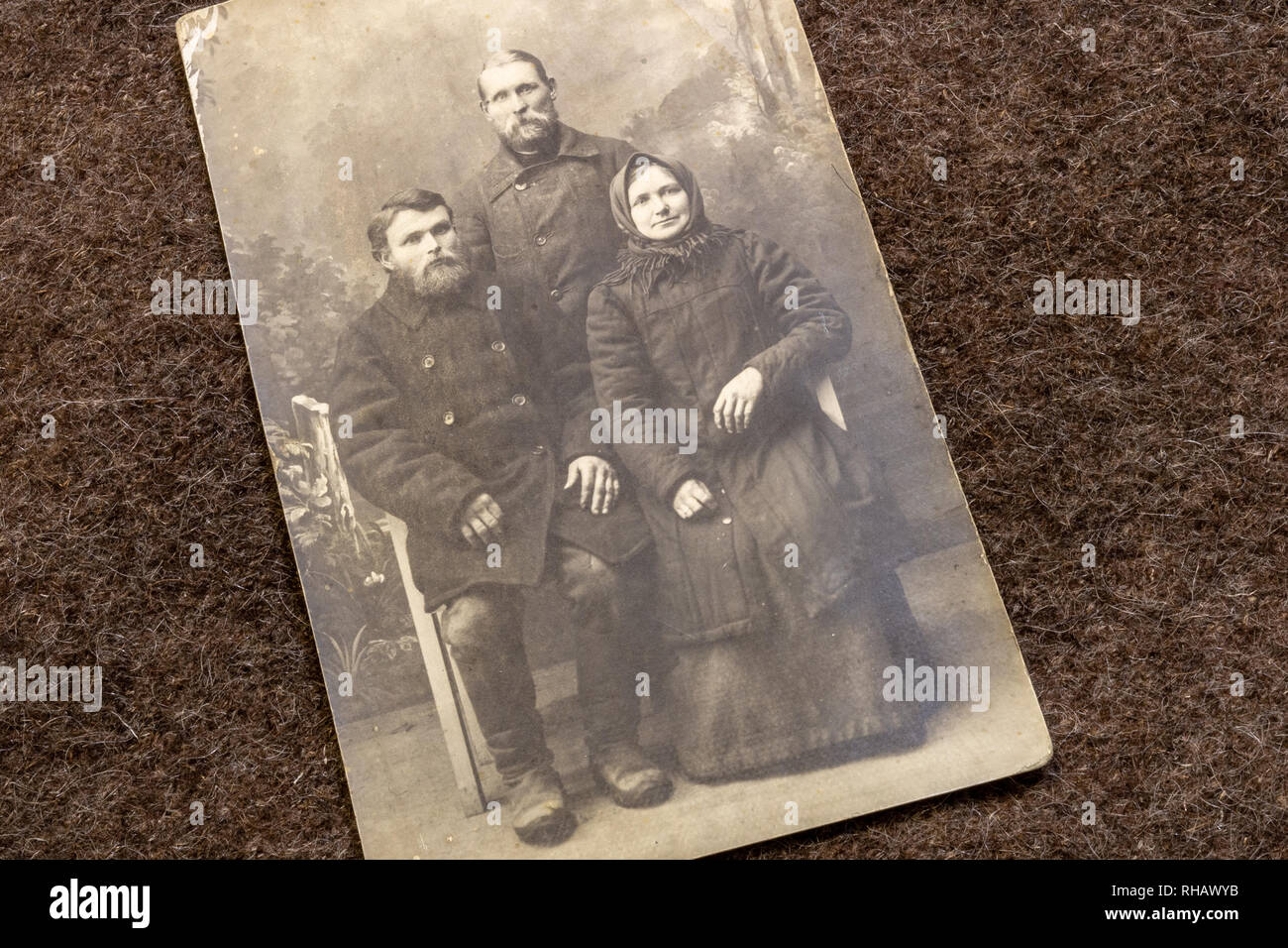 Postcard of poor family in period of World War I on trench coat background - Stock Image