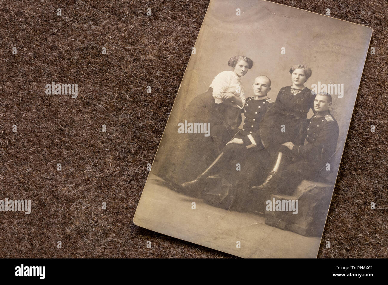 Portrait of officers and their girlfriends in period of World War I on trench coat background - Stock Image