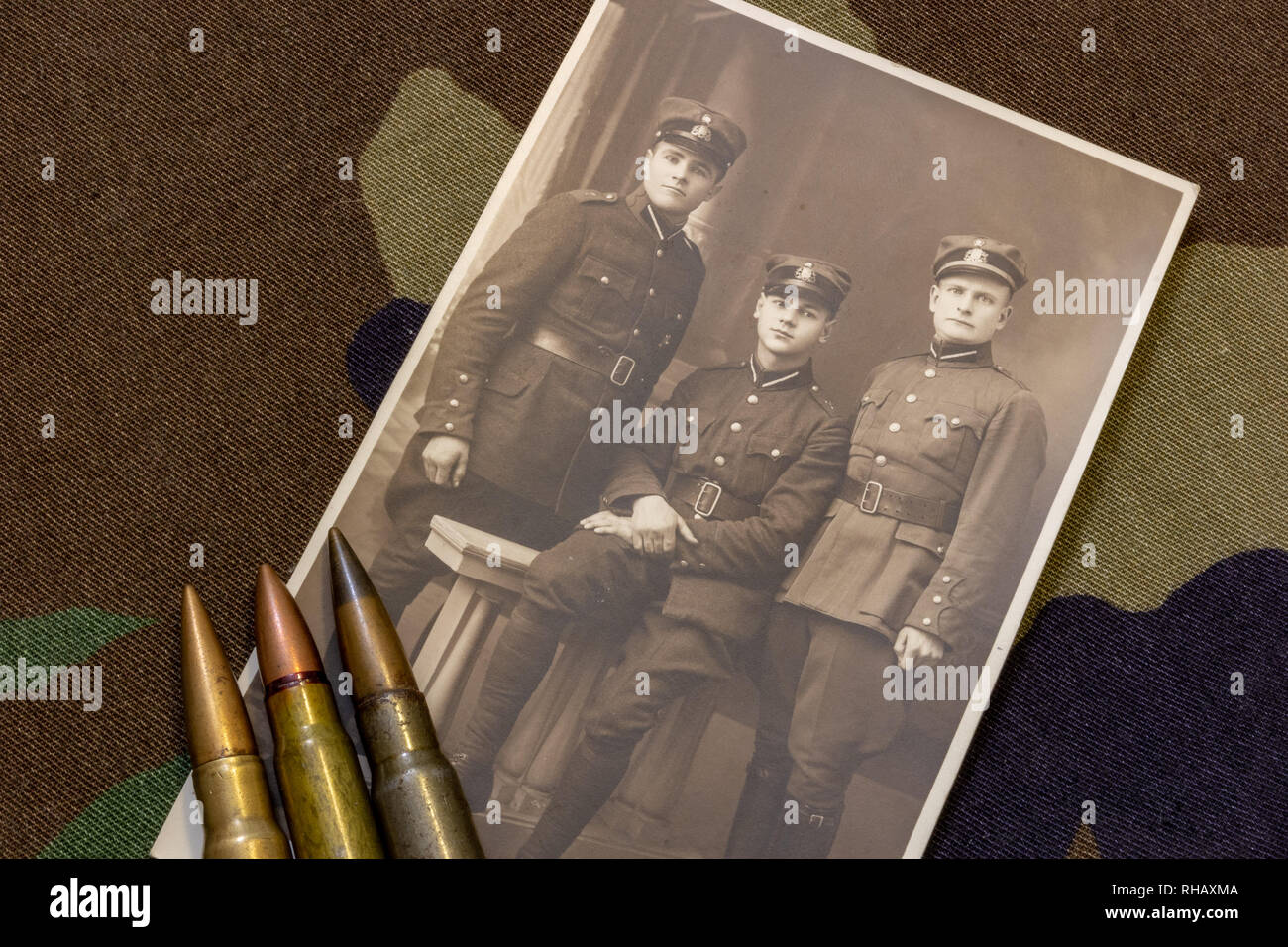 Postcard of three Latvian soldiers in period around 1935 and rifle bullets on trench coat - Stock Image