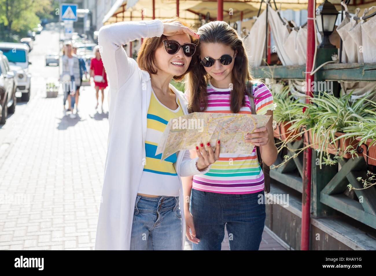 Mom and daughter tourist looking at the map on the street of european city, travel to Europe - Stock Image
