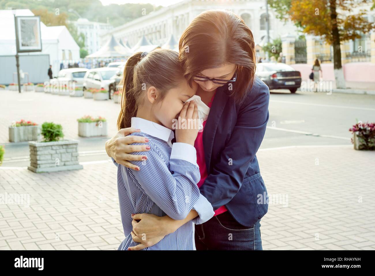 Mother consoling her crying daughter. Urban background - Stock Image