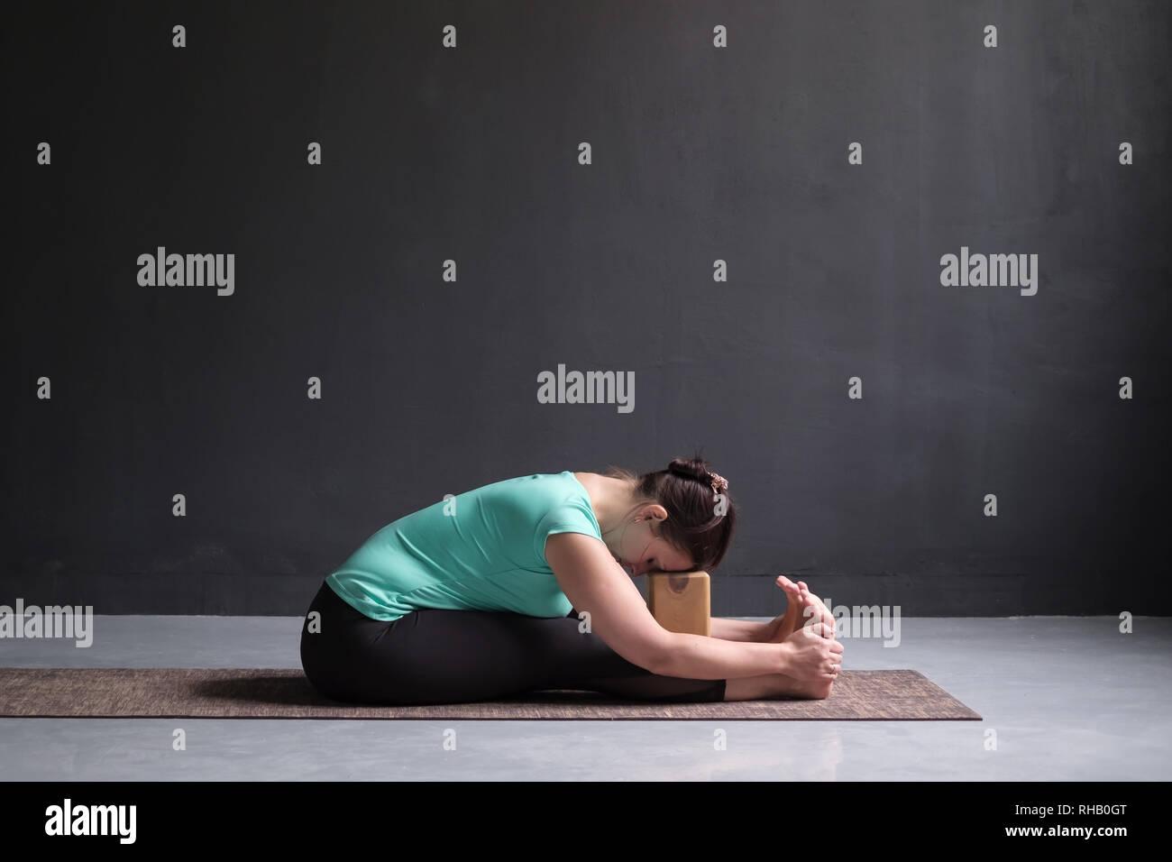 woman practicing yoga, Seated forward bend pose, using brick or block - Stock Image