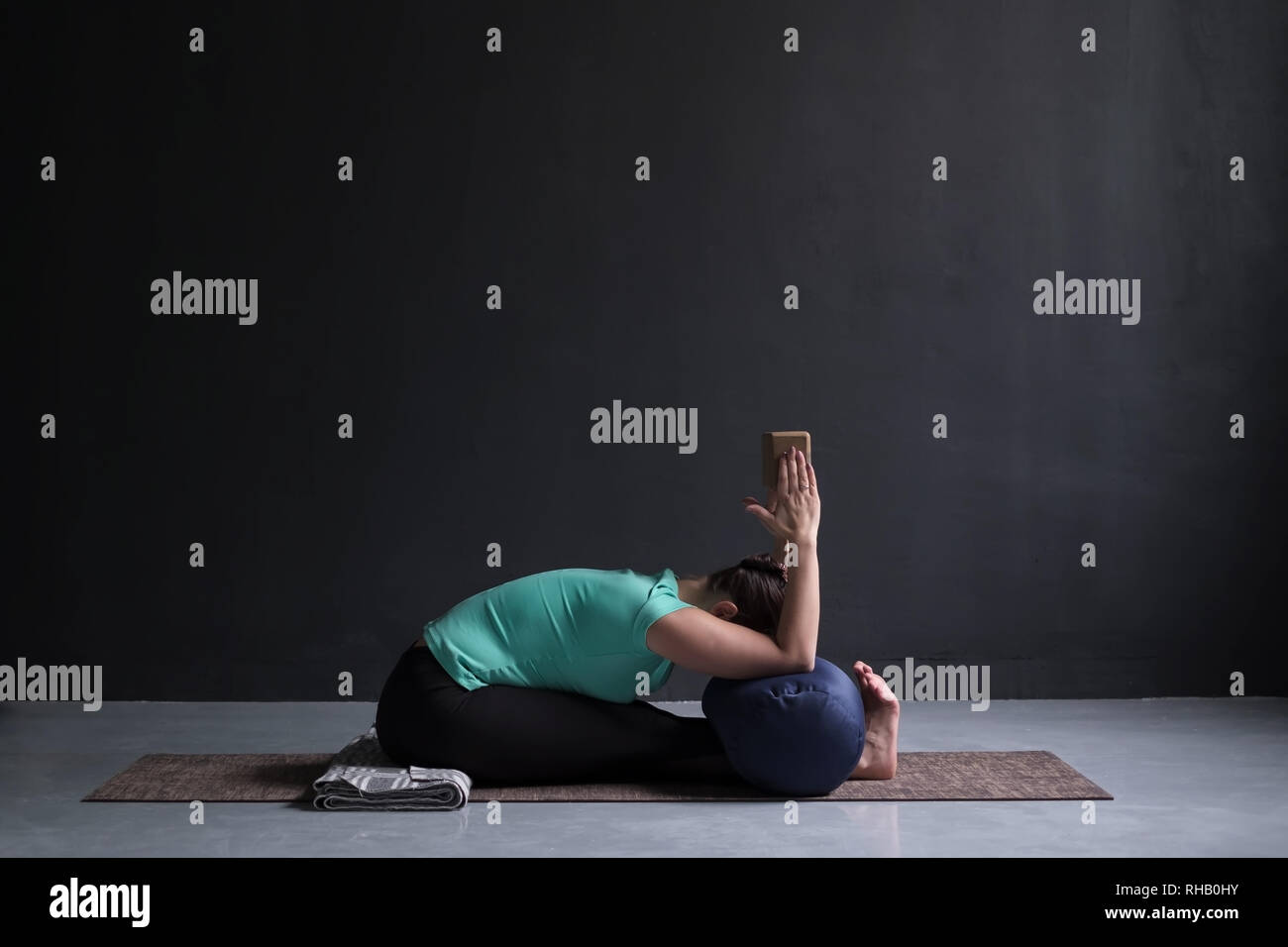 woman practicing yoga, Seated forward bend pose, using block and bolster - Stock Image