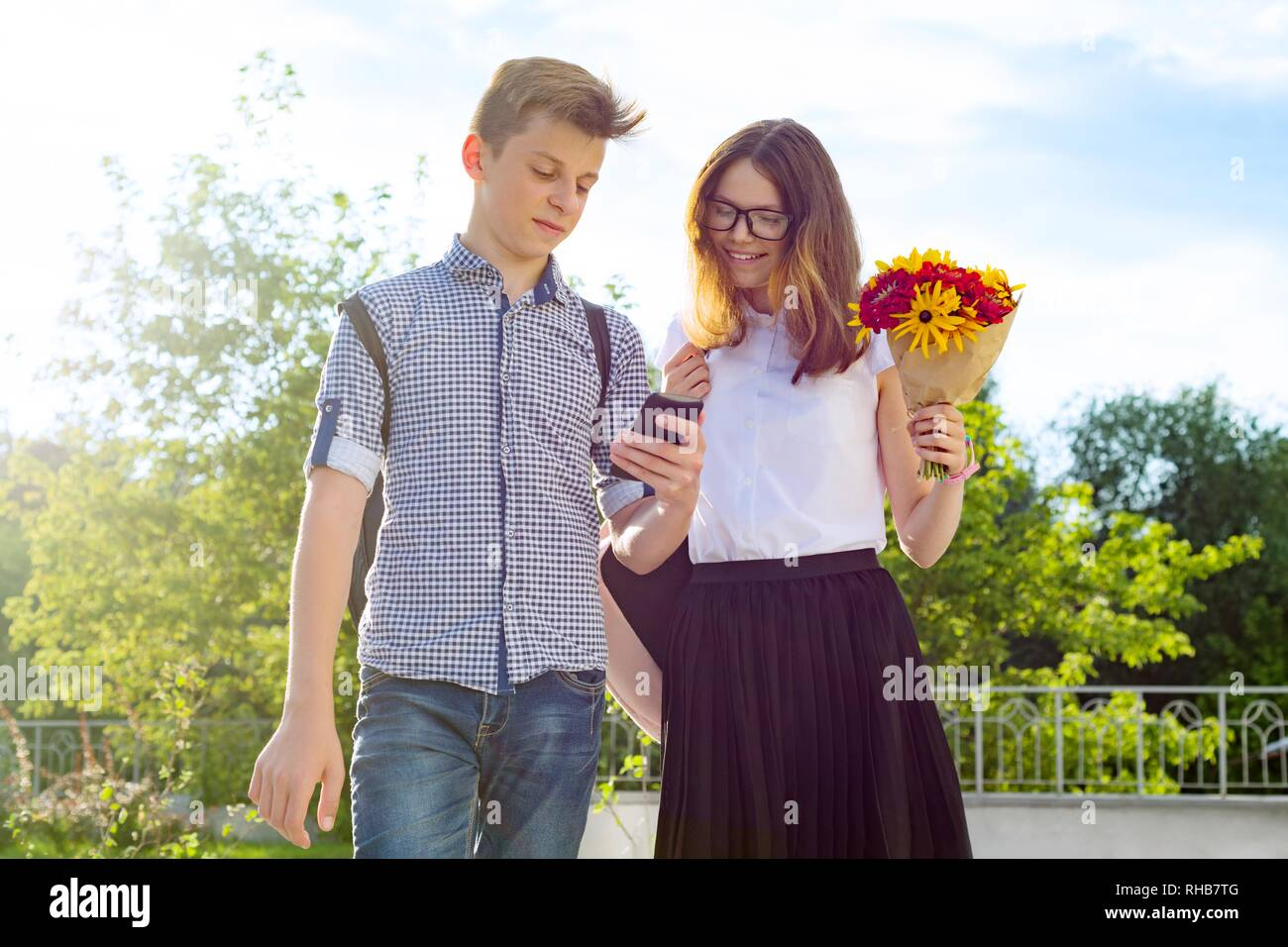 Back to school, Children teenagers go first day to school, with bouquet of flowers, smile, talk - Stock Image