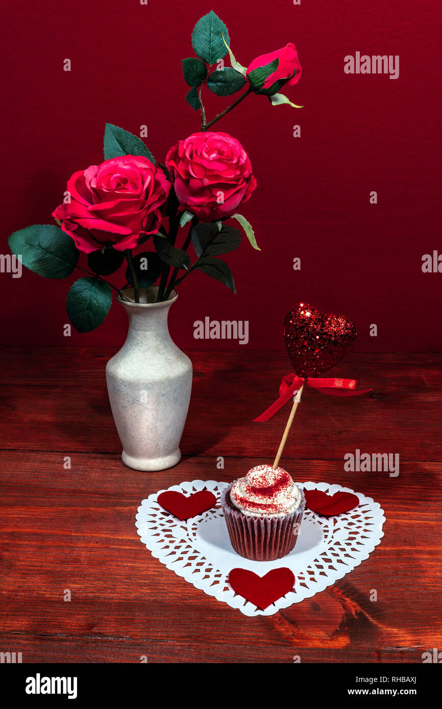 Beautiful pink roses in a vase, heart shapped white dollie with a decorated cup cake on it with a heart on a pick. Stock Photo