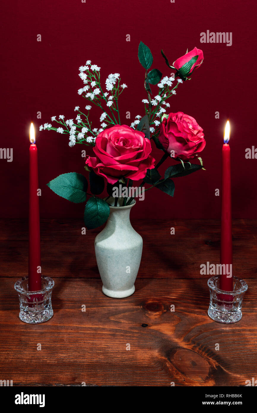 Beautiful pink roses in a vase acsented with Baby's Breath flowers, Two red candles in crystal holder. Stock Photo