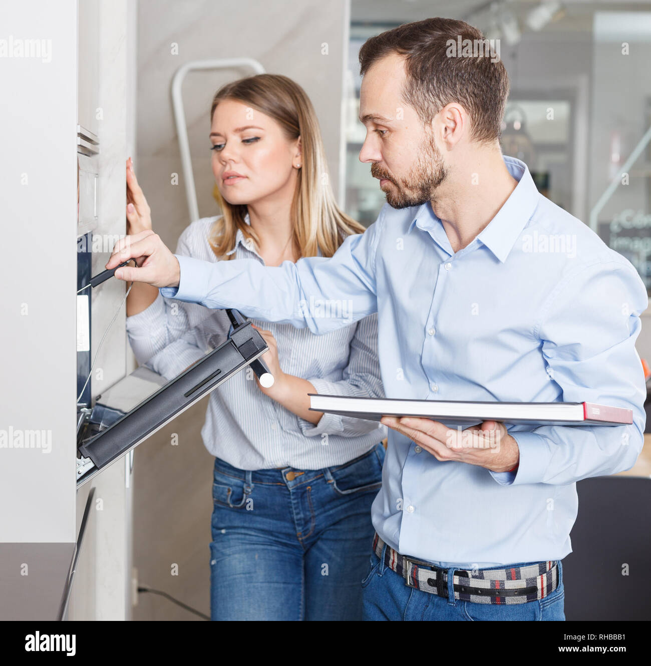 Young couple standing with cookbook in stylish kitchen near open oven, controlling temperature with probe - Stock Image