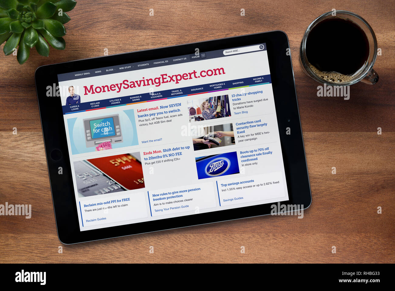The website of MoneySavingExpert is seen on an iPad tablet, on a wooden table along with an espresso coffee and a house plant (Editorial use only). Stock Photo