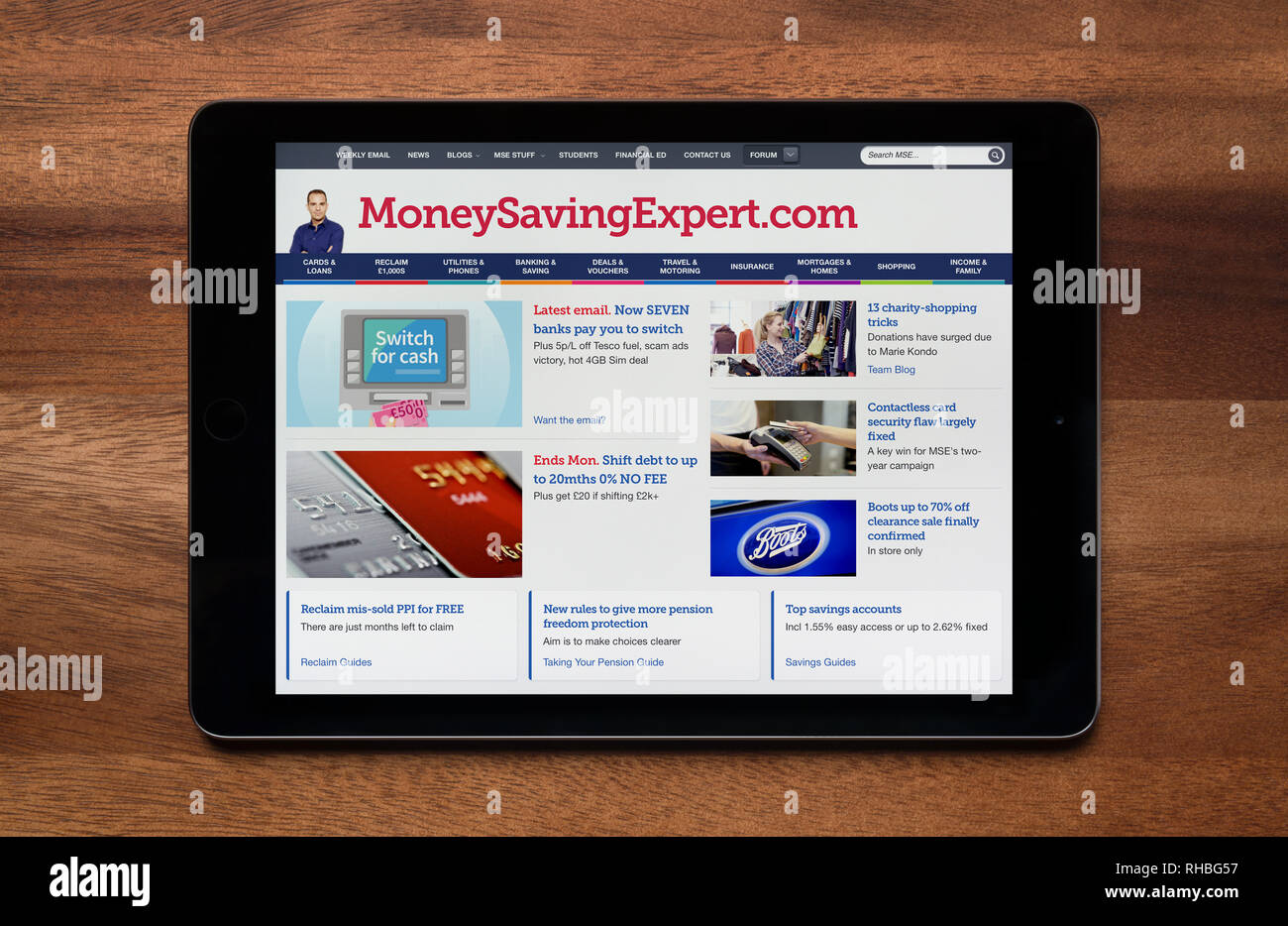 The website of MoneySavingExpert is seen on an iPad tablet, which is resting on a wooden table (Editorial use only). Stock Photo