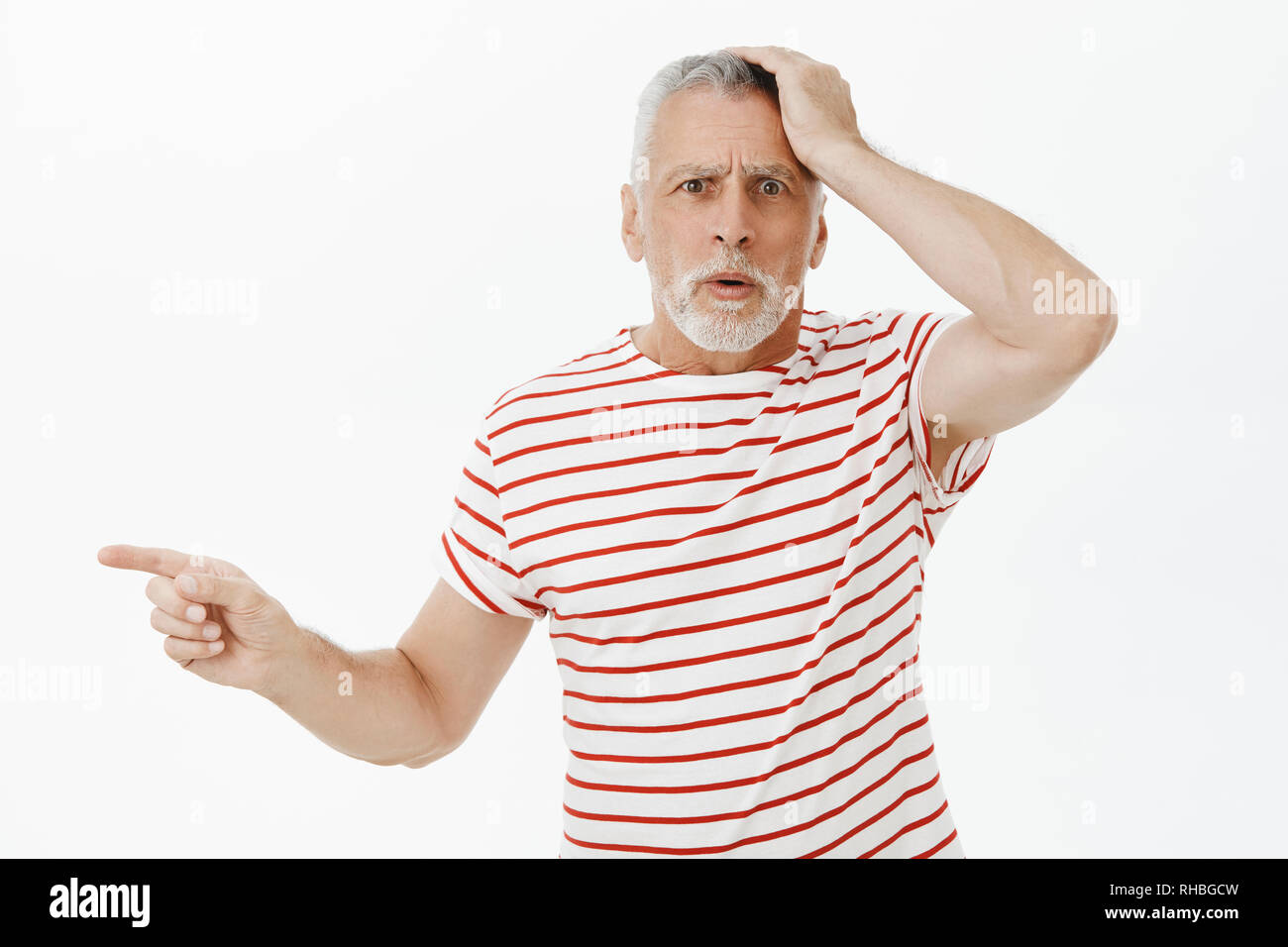 Portrait of concerned and confused senior man being fooled standing troubled and questioned holding hand on head frustrated pointing left cannot - Stock Image