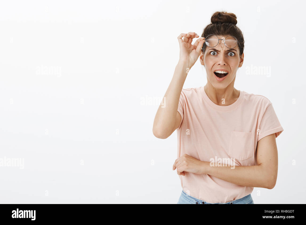 What heck. Portrait of shocked concerned and insulted young bothered woman taking off glasses, frowning and grimacing in disapproval and shook - Stock Image