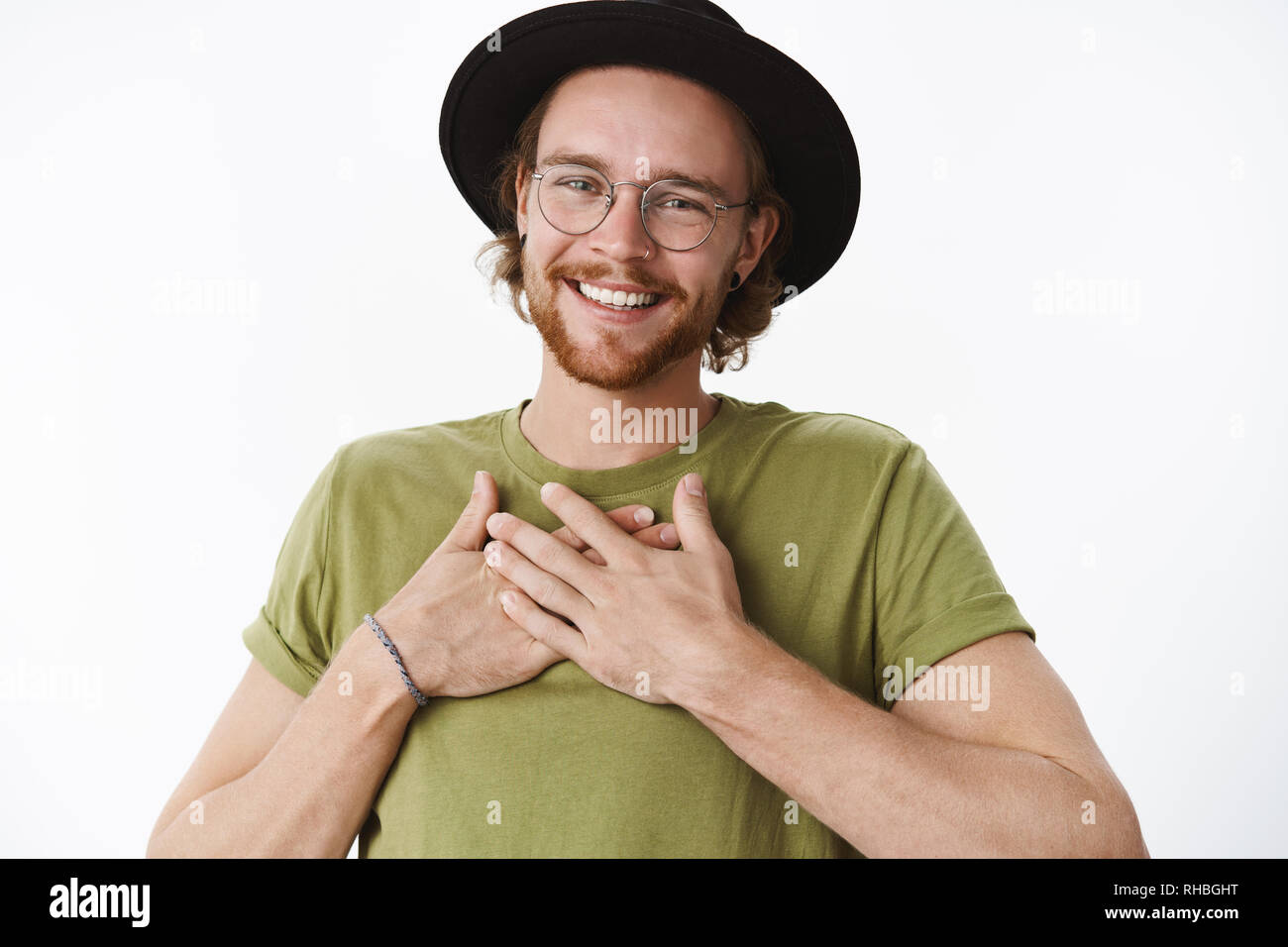 Oh thanks you should not have. Portrait of touched and delighted bday man with glasses, pierced nose and hat holding hands on body and smiling - Stock Image