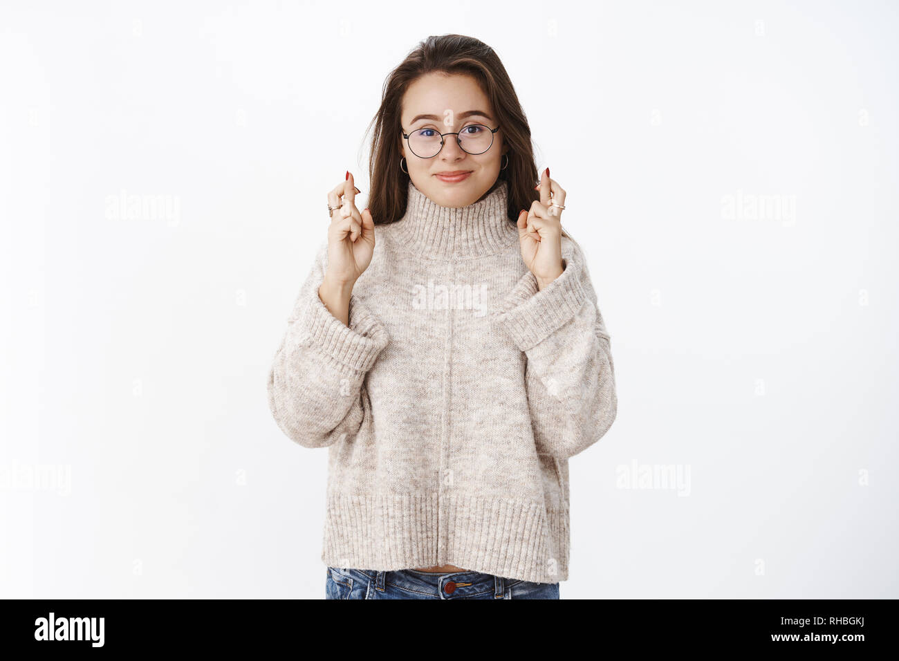 Studio shot of optimsitic happy and thrilled young woman in glasses and  sweater cross fingers for de3c68806523