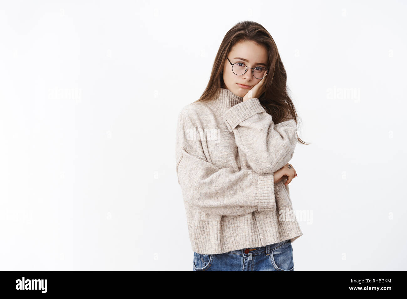 Portrait of tired and drained cute female freelancer in sweater and pc glasses leaning head on palm looking upset and exhausted at camera as having - Stock Image