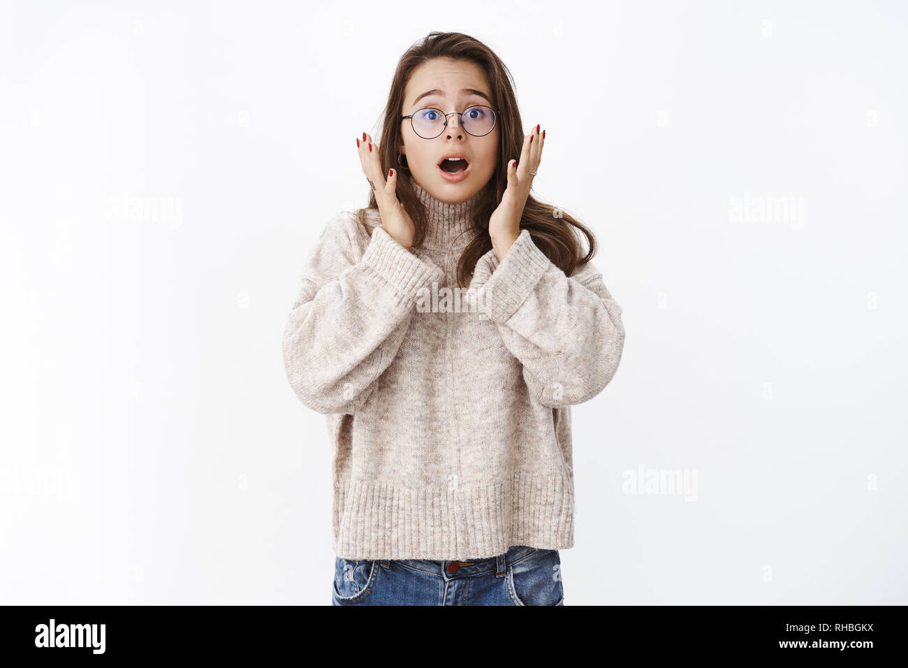 Worried and shocked cute woman showing empathy and shook as reacting to amazing terrible news open mouth and raising eyebrows with eyes in surprise Stock Photo