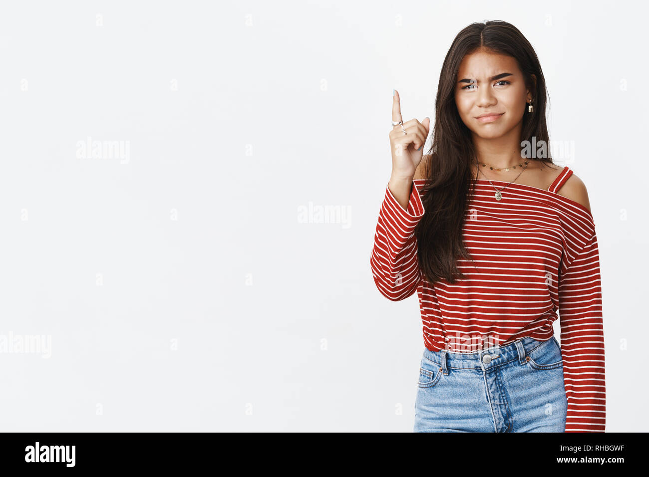 Displeased and gloomy young female adolescent grimacing from sadness of regret making disappointed face showing number one or pointing up at something - Stock Image