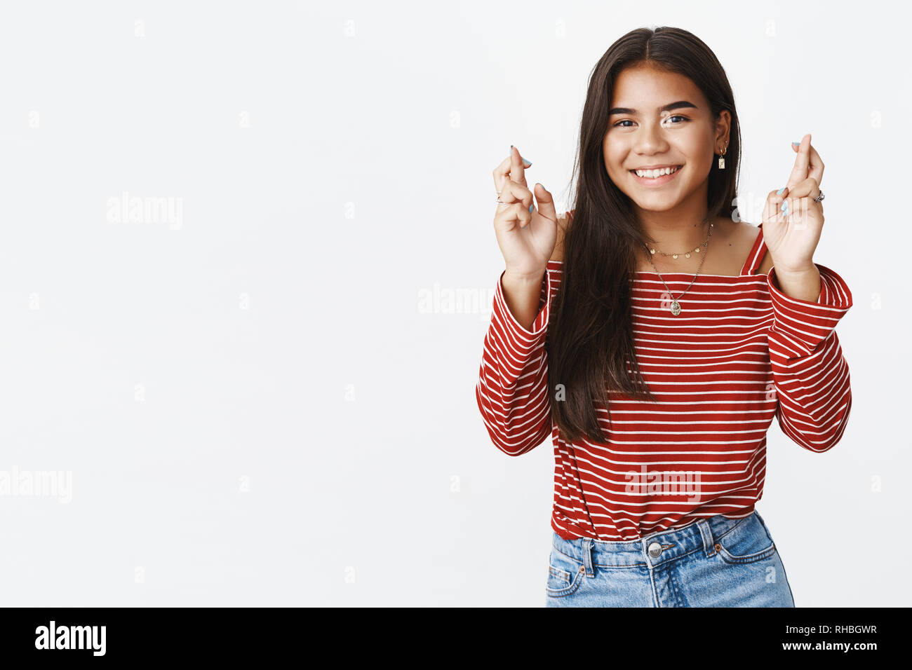 Charming hopeful and optimistic young woman believe dream come true crossing fingers for good luck and smiling positive at camera making wish - Stock Image