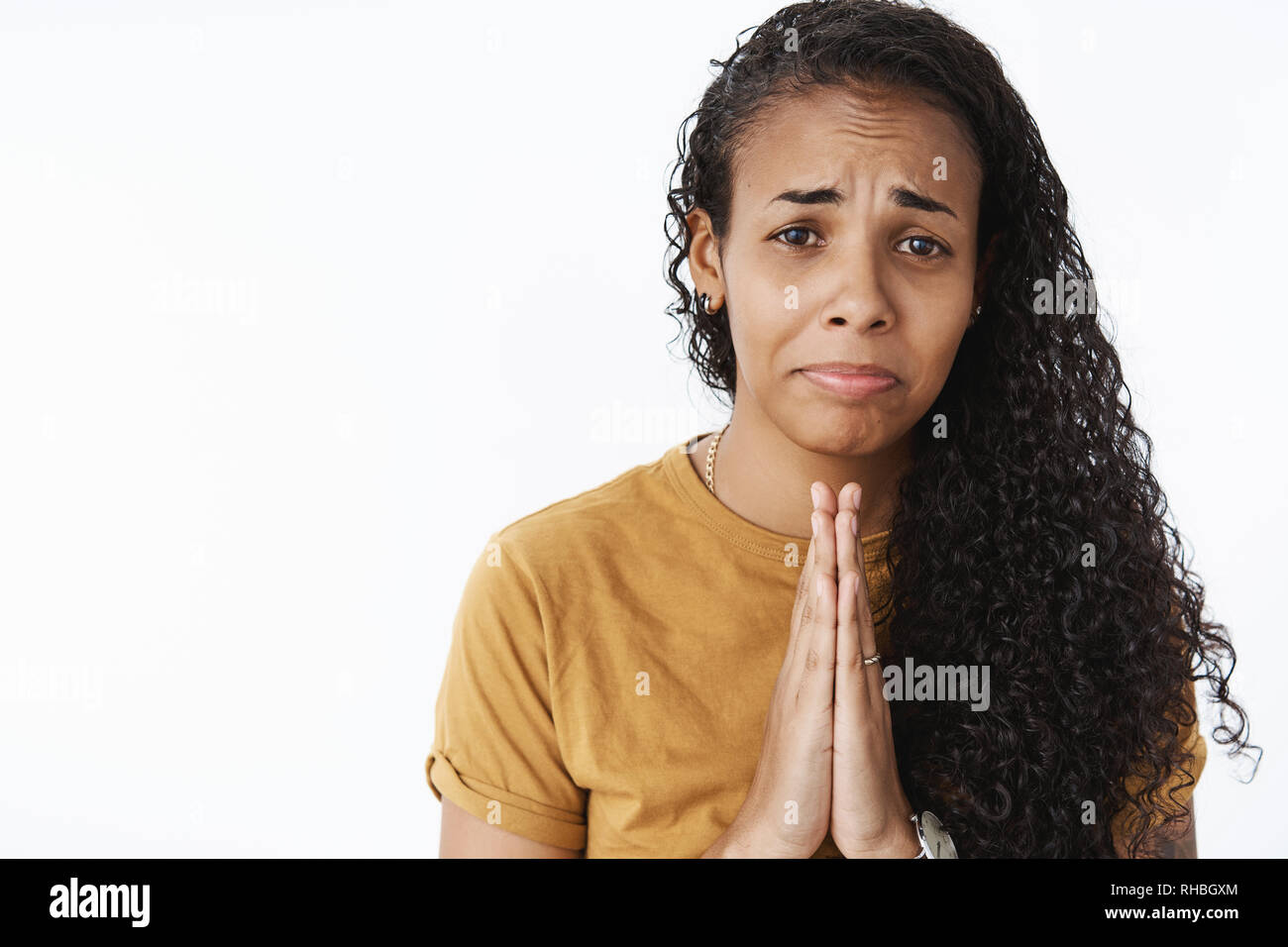 Please I need you. Portrait of whining silly and sad young cute african-american girl with long curly hair holding hands in pray, crying and grimacing - Stock Image