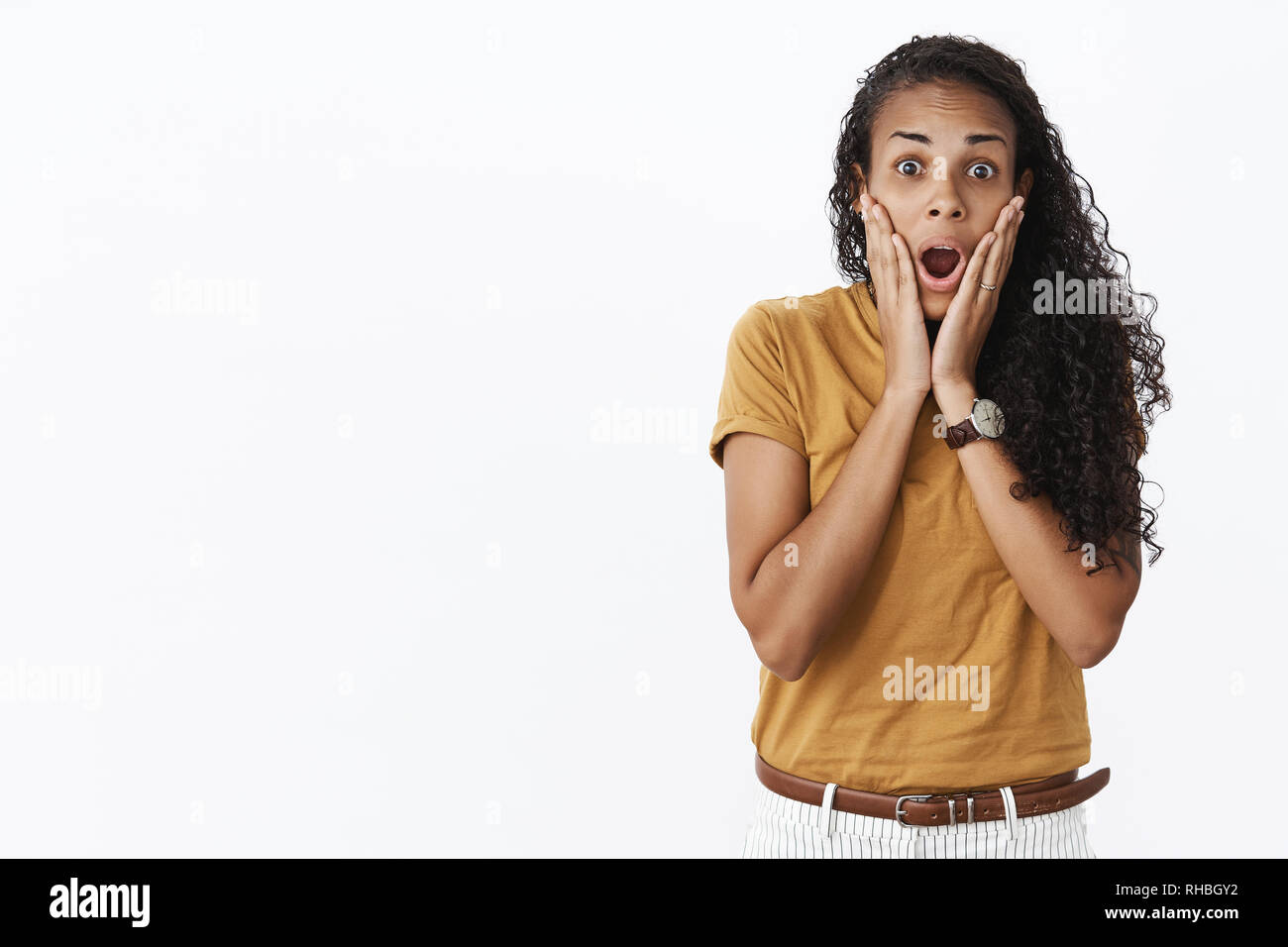 Surprised african american girl grabbing face with hands dropping jaw as being astonished by unexpected things happen gasping amazed popping eyes at - Stock Image