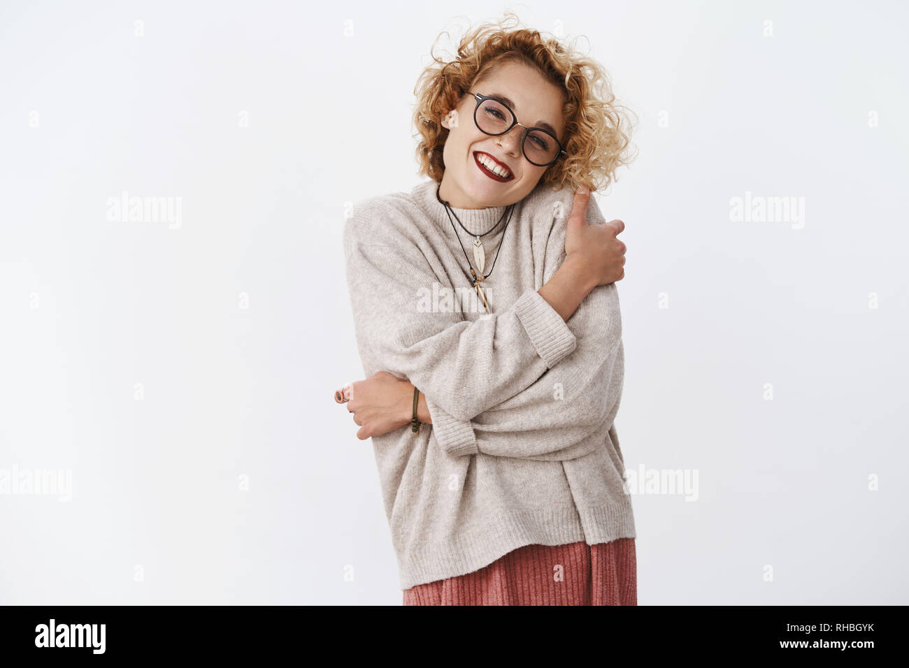 Charming happy and tender girlfriend giggling happily hugging herself as wearing comfy warm sweater leaning head on shoulder lovely smiling at camera - Stock Image