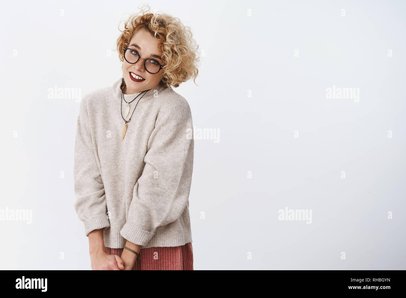Portarit of cute and shy flirty blond girl in glasses and sweater making lovely gazes at camera smiling sensually and feminine as posing over white - Stock Image