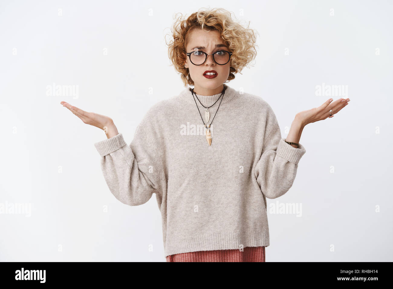 What hell was that, explain. Frustrated and questioned woman in dismay and confusion raise hands sideways and shrugging lifting eyebrow in questioned - Stock Image