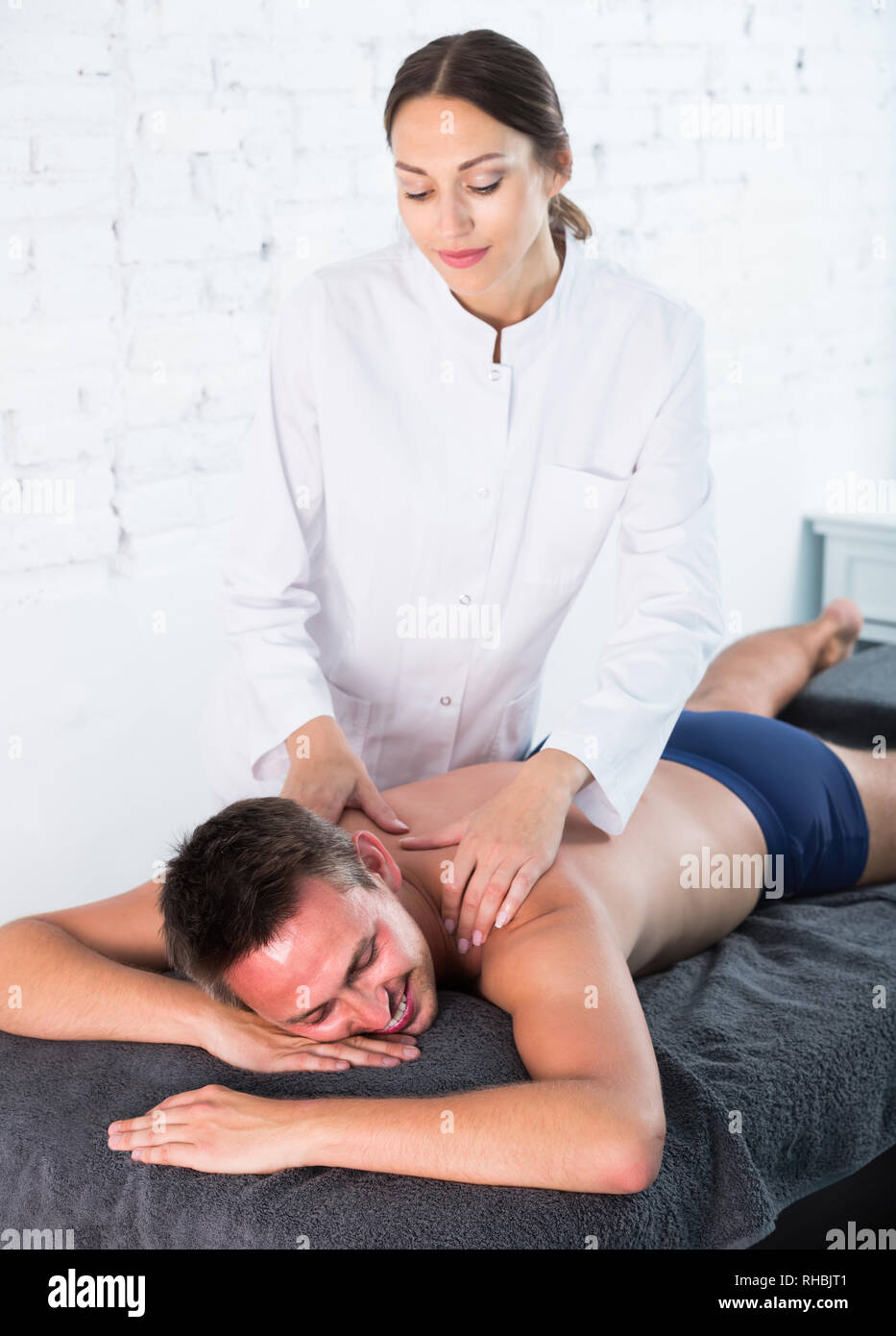 Professional masseuse performing back massage to positive swiss  male client in spa center Stock Photo