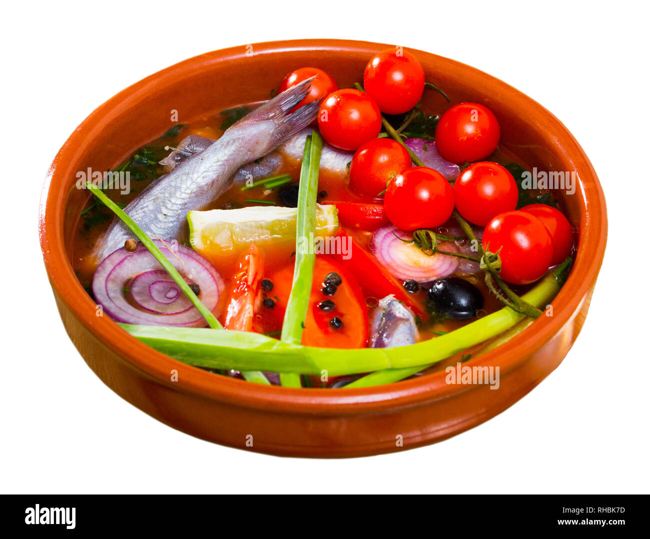 Fisher soup from whiting with tomatoes, red onion, bell pepper served with lemon, scallions, black olives. Isolated over white background - Stock Image