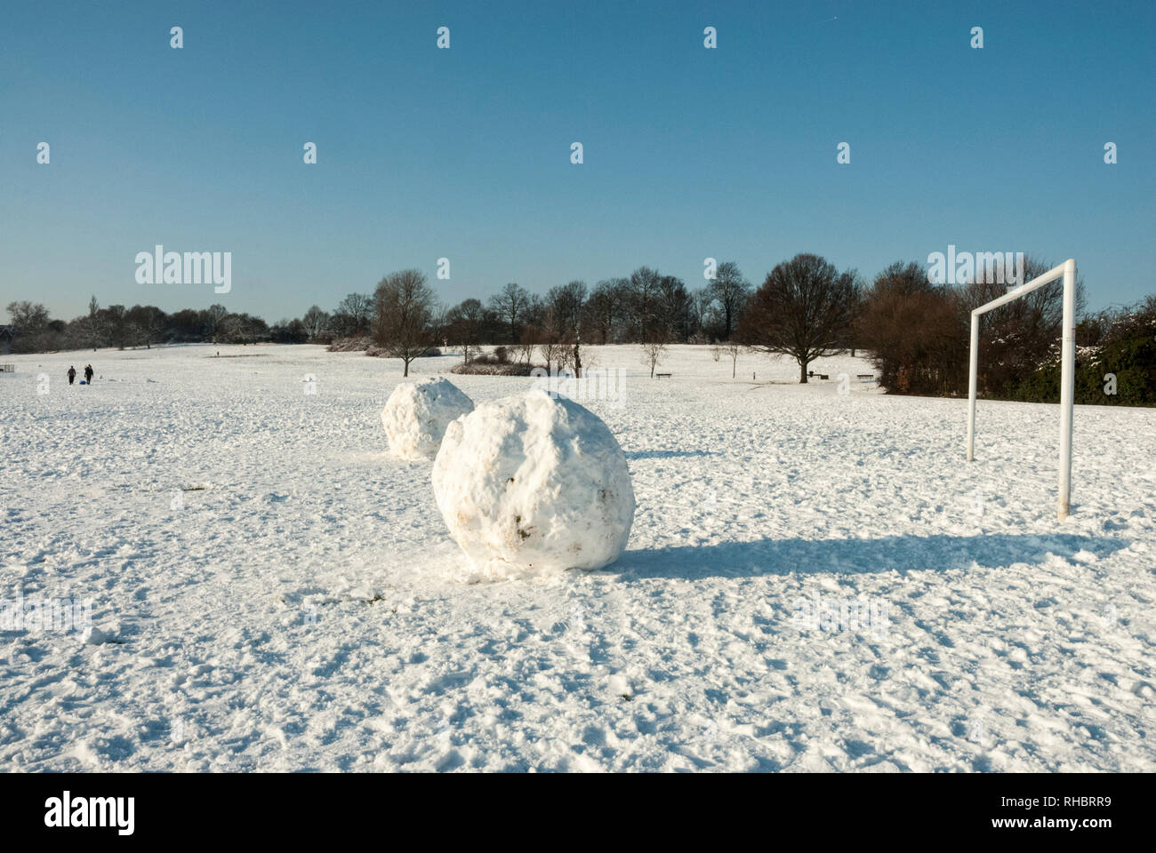 Enormous snowballs in front of an open goal on snow covered sunny Hampstead Heath, play with the concept of scale. - Stock Image