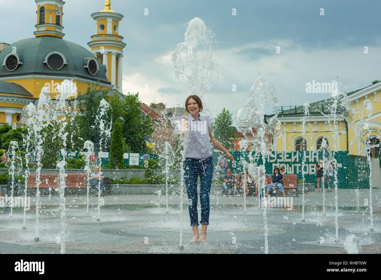 Kyiv UA, 19-07-2018. Young teenage girl in fountain. Girl happy, clothes wet, background city architecture - Stock Image