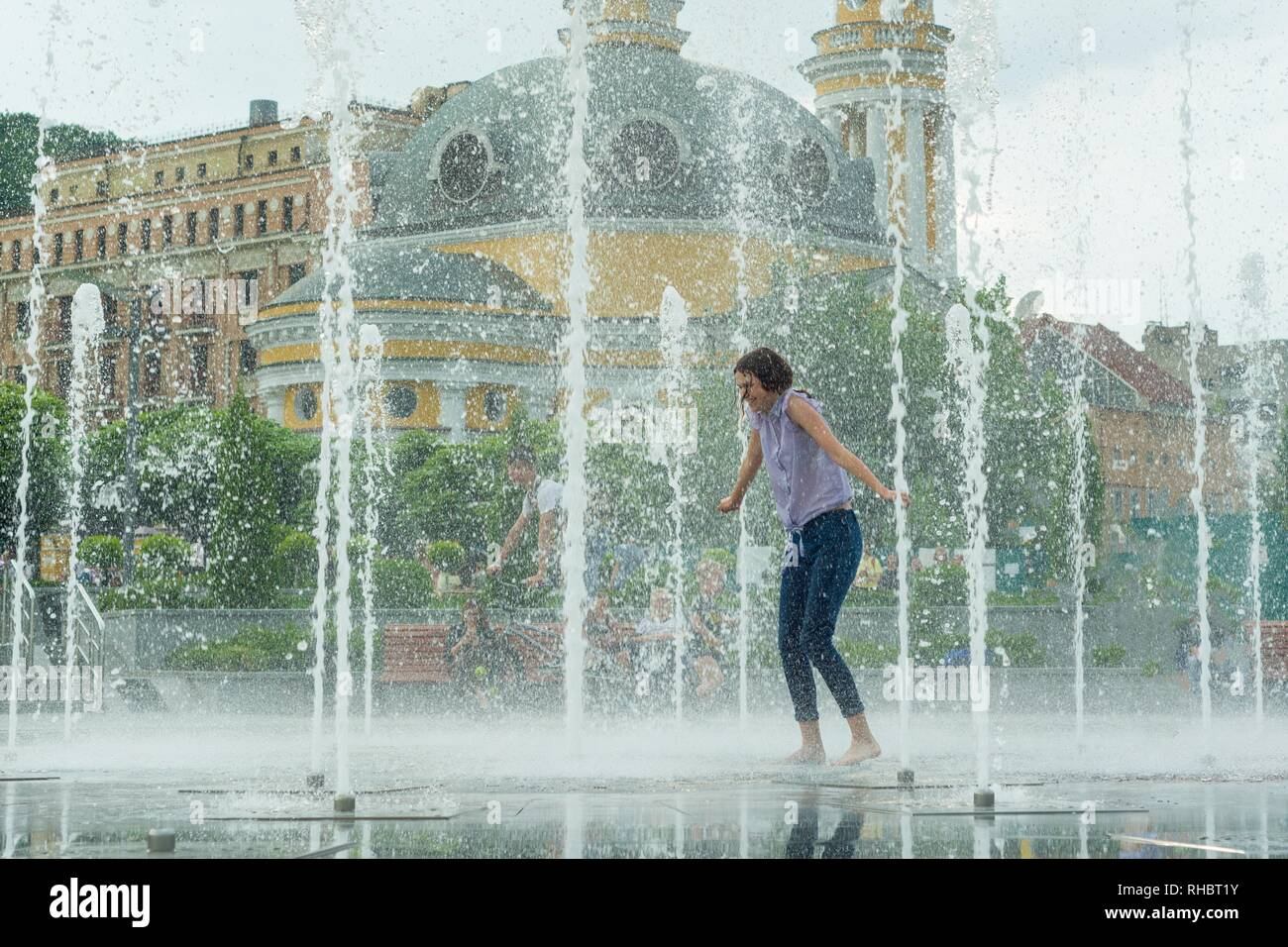 Young teenage girl in fountain. Girl happy, clothes wet, background city architecture - Stock Image