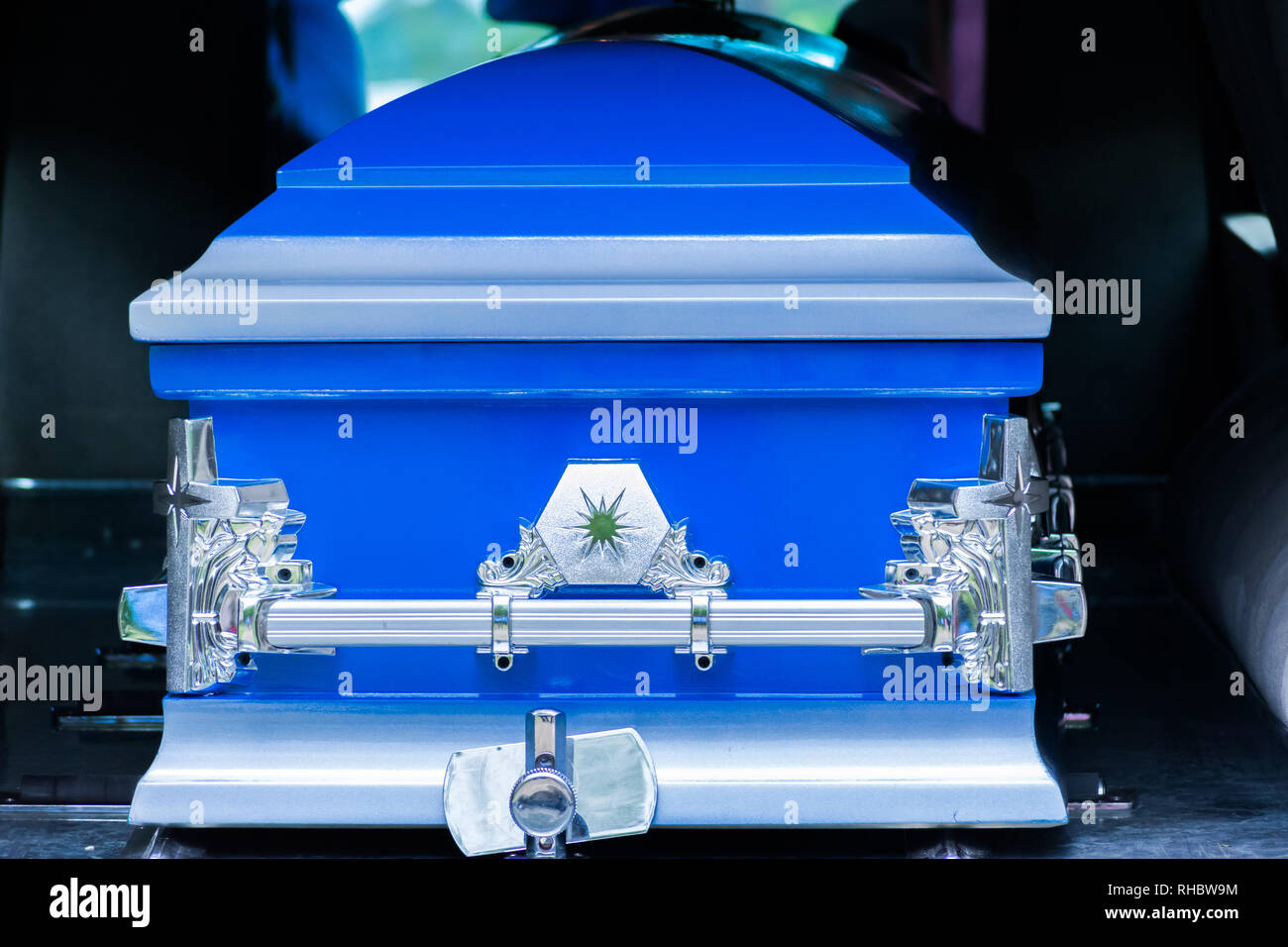Closed blue and silver coffin/casket in back of hearse before cemetery burial - Stock Image