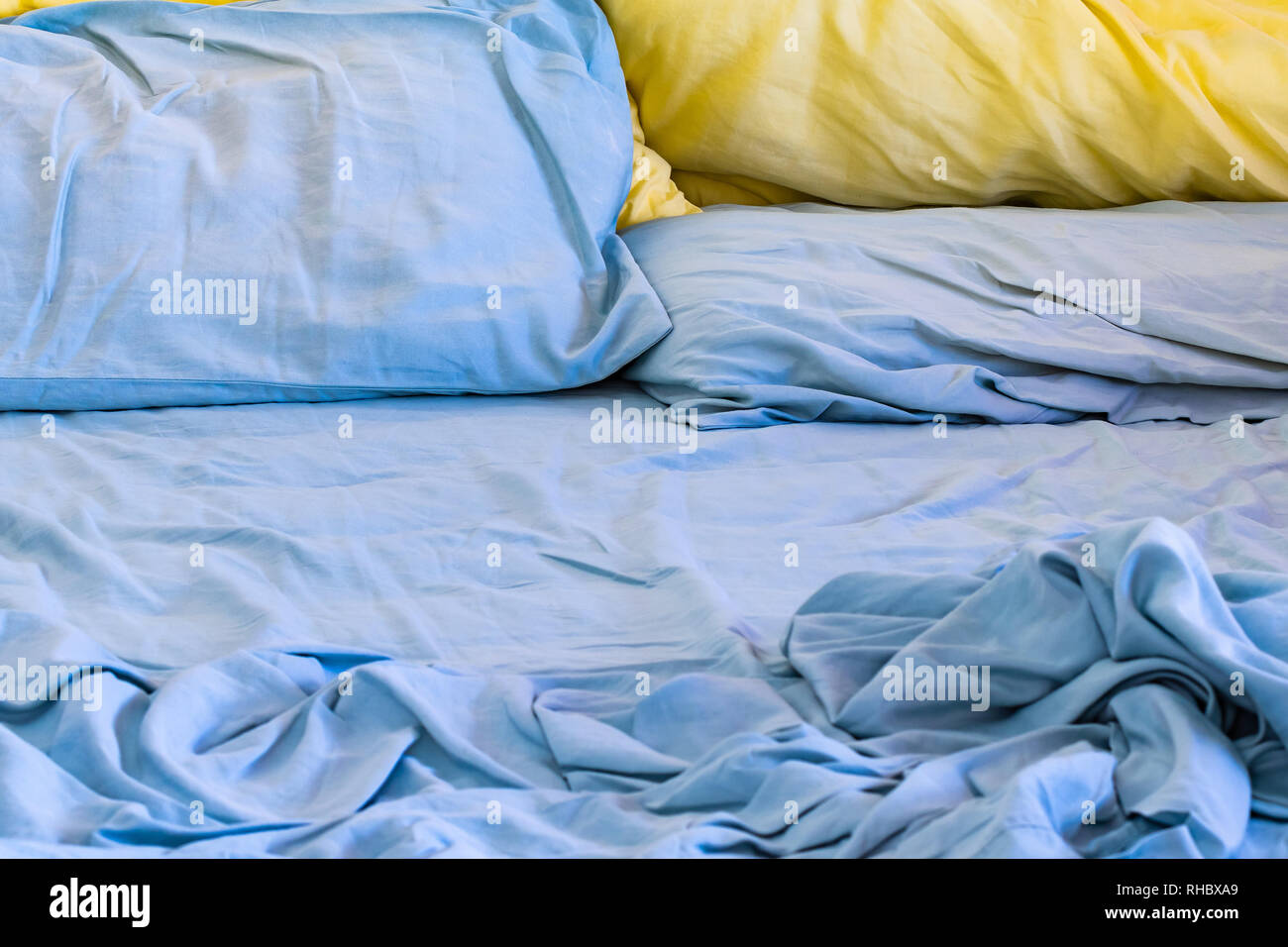 Messy unmade bed with blue sheets and blue and yellow pillows - Stock Image