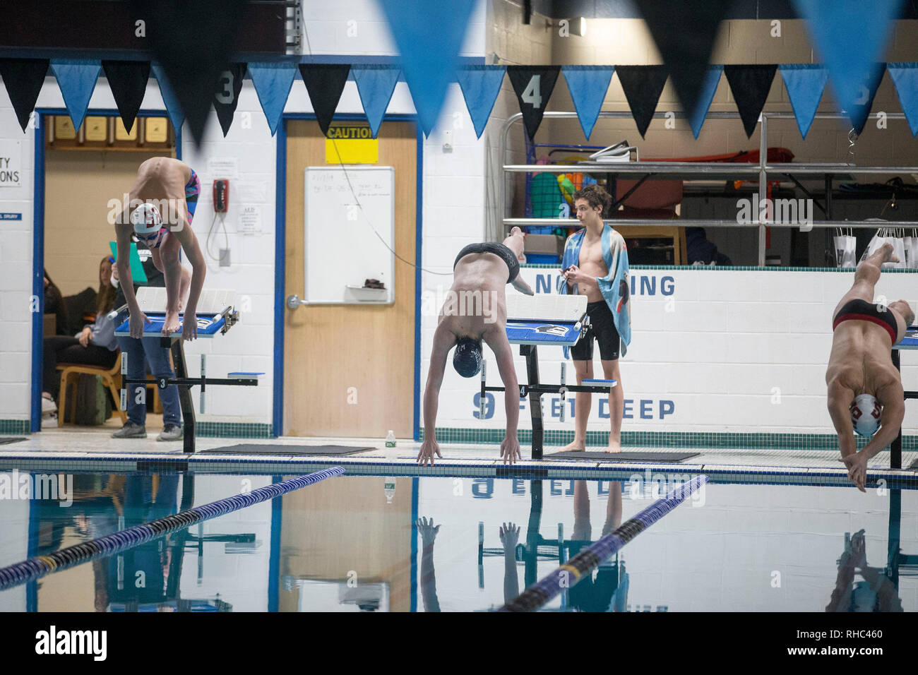 Swimmers at the start of a high school swim meet - Stock Image